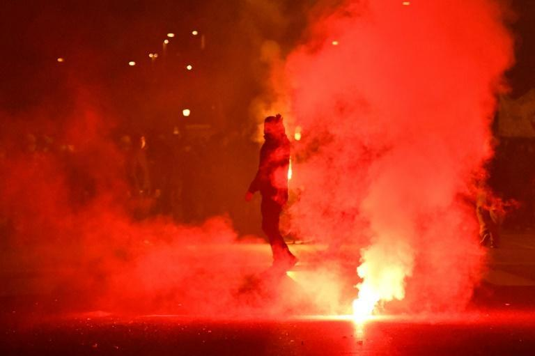 A left-wing activist walks past flares as they take part in a protest rally to demand economic support measures, as the government announced a new series of restrictions to contain the spread of Covid-19 and considers more stringent measures, in Rome