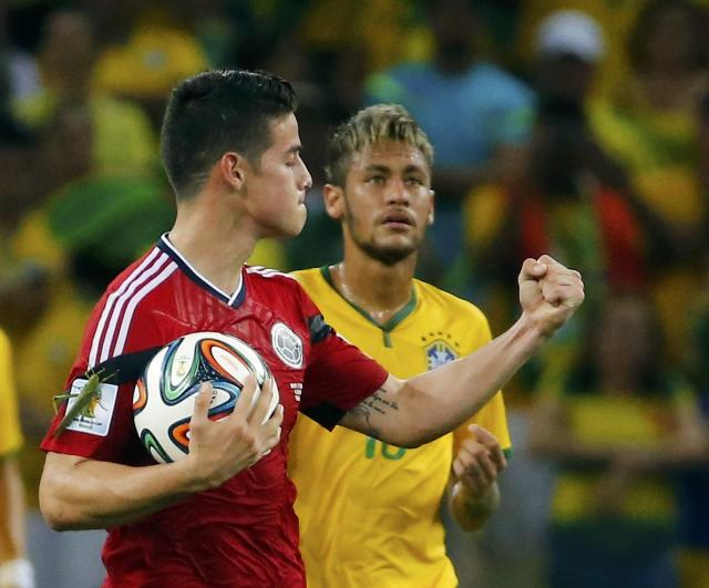 Colombia's James Rodriguez celebrates next to Brazil's Neymar after scoring a penalty against Brazil during their 2014 World Cup quarter-finals at the Castelao arena in Fortaleza July 4, 2014. REUTERS/Yves Herman (BRAZIL - Tags: SOCCER SPORT WORLD CUP TPX IMAGES OF THE DAY)