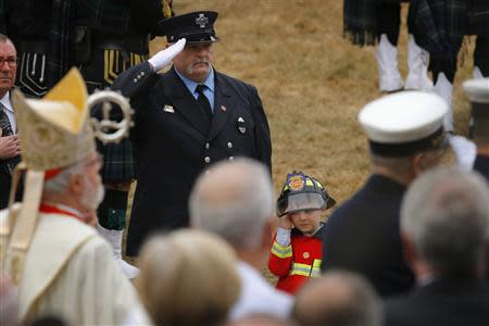Robert (R), nephew of Boston Fire Department Lieutenant Edward Walsh, salutes as his uncle's casket is carried out of Saint Patrick's church following his funeral in Watertown, Massachusetts April 2, 2014. REUTERS/Brian Snyder