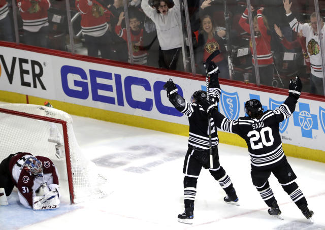 Chicago Blackhawks defenseman Duncan Keith (2) celebrates with left wing Brandon Saad (20) after scoring against Colorado Avalanche goalie Philipp Grubauer during overtime in an NHL hockey game Sunday, March 24, 2019, in Chicago. The Blackhawks won 2-1. (AP Photo/Nam Y. Huh)