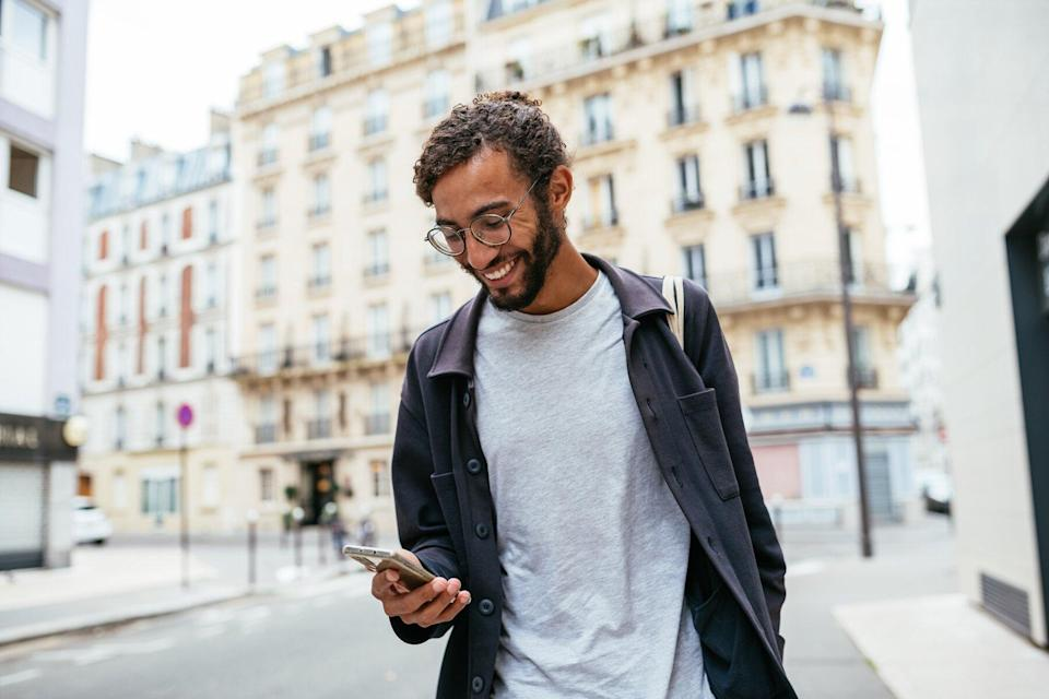 Modern young man with curly hair in the city looking at his smartphone