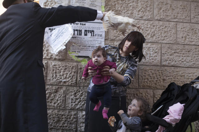 <p>An ultra-Orthodox Jewish man swings a chicken over his family as they perform the Kapparot ceremony on Sept. 27, 2017 in Jerusalem, Israel. It is believed that the Jewish ritual, which involves swinging a live chicken above one's head, transfers the sins of the past year to the chicken, which is then slaughtered and traditionally given to the poor. It is performed before the Day of Atonement, or Yom Kippur, the most important day in the Jewish calendar, which this year will start on sunset on September 29. (Photo: Lior Mizrahi/Getty Images) </p>