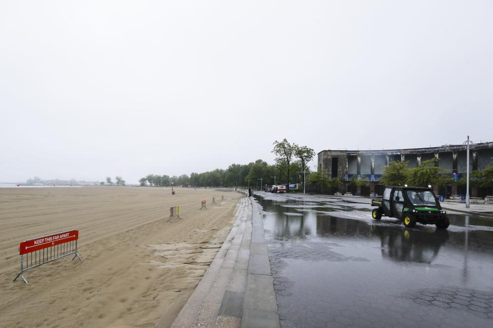New York City Parks officials work at an empty Orchard Beach Saturday, May 23, 2020, in the Bronx borough of New York. Gov. Andrew Cuomo has given New Yorkers an unexpected reprieve from cabin fever by easing the state's ban on gatherings due to coronavirus concerns, in time for the Memorial Day weekend. New York City beaches are open this weekend. But no swimming is allowed, and masks must be worn. (AP Photo/Frank Franklin II)