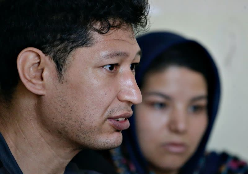 Afghan refugees speak during an interview at their rented house in Ciawi