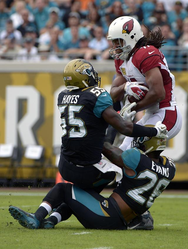 Arizona Cardinals wide receiver Larry Fitzgerald (11) falls backward over the goal line to score a touchdown on a 14-yard pass as he is tackled by Jacksonville Jaguars outside linebacker Geno Hayes (55) and free safety Josh Evans (26) during the first half of an NFL football game in Jacksonville, Fla., Sunday, Nov. 17, 2013. (AP Photo/Phelan M. Ebenhack)