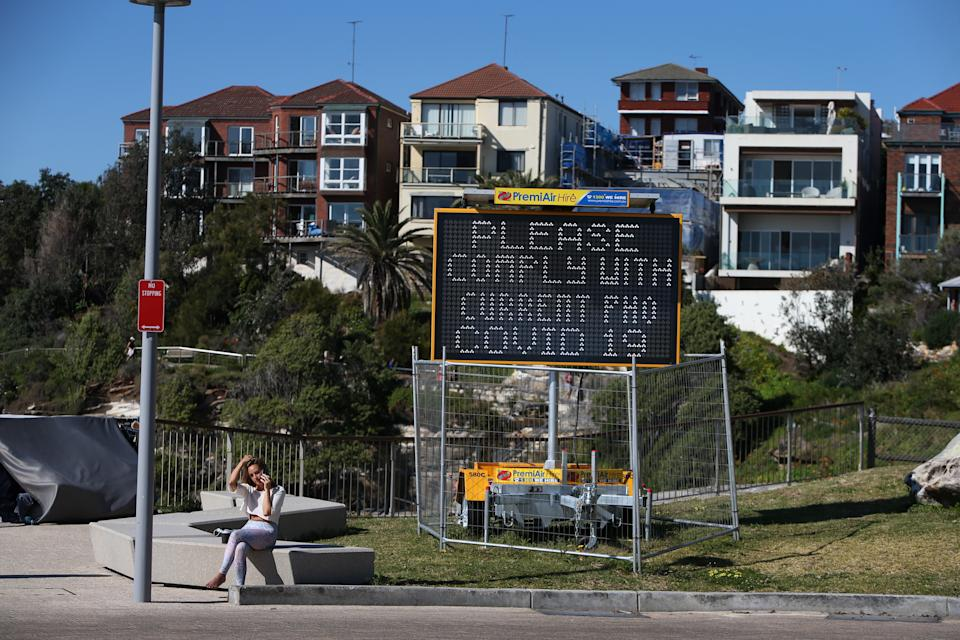A person sits talking on their phone near a Covid-19 public notice sign at Sydney's Bondi Beach on September 24. 2021.