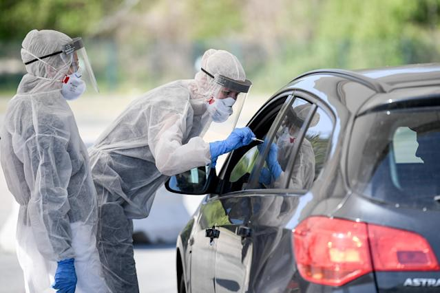 23 April 2020, Berlin: Employees from the Health Department hold a swab in a car window in the outpatient drive-in coronavirus test facility. Photo: Britta Pedersen/picture alliance via Getty Images.