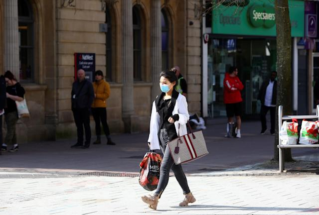 A woman wearing a mask walks through Cardiff. (Getty Images)