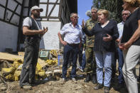 German Chancellor Angela Merkel, front second right, gestures as she and the Governor of the German state of Rhineland-Palatinate, Malu Dreyer, front right, talk to a resident in Schuld, western Germany, Sunday, July 18, 2021 during their visit in the flood-ravaged areas to survey the damage and meet survivors. After days of extreme downpours causing devastating floods in Germany and other parts of western Europe the death toll has risen. (Christof Stache/Pool Photo via AP)