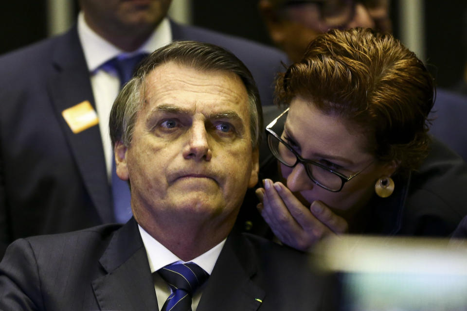 "In this May 29, 2019 handout photo provided by Agencia Brasil, Brazil's President Jair Bolsonaro listens as Carla Zambelli whispers into his ear during a meeting at Congress, in Brasilia, Brazil. Several weeks after publishing explosive reports on a top member of Brazil's far-right government, U.S. journalist Glenn Greenwald sat before the Human Rights and Minorities Commission. During the June 25 hearing Zambelli told Greenwald: ""If you don't prove this information, it is fake and you're a liar. If it's true, then you're a criminal because you hacked someone's phone."" (Marcelo Camargo/Agencia Brasil via AP)"