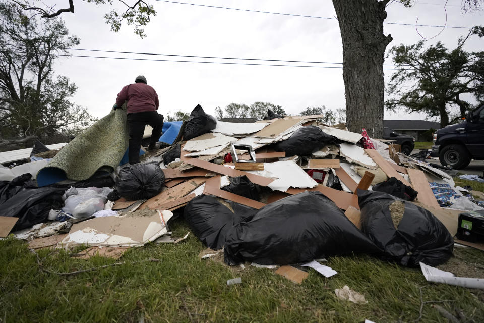 Khalif Kinnie throws debris on a pile from a heavily damaged home he was hired to gut, in the aftermath of Hurricane Laura and Hurricane Delta, in Lake Charles, La., Friday, Dec. 4, 2020. (AP Photo/Gerald Herbert)