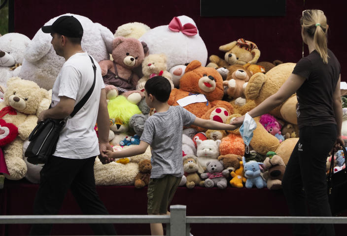 A family walk past toys brought by people near a school after a shooting on Tuesday in Kazan, Russia, Thursday, May 13, 2021. Russian officials say a gunman attacked a school in the city of Kazan and Russian officials say several people have been killed. Officials said the dead in Tuesday's shooting include students, a teacher and a school worker. Authorities also say over 20 others have been hospitalised with wounds. (AP Photo/Dmitri Lovetsky)