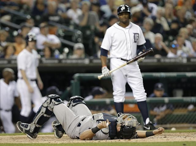 New York Yankees catcher Francisco Cervelli lies at home plate after being hit by a pitch as Detroit Tigers' Rajai Davis looks on in the fifth inning of a baseball game in Detroit, Wednesday, Aug. 27, 2014. (AP Photo/Paul Sancya)