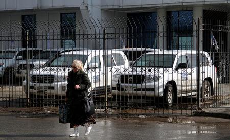 A woman walks past vehicles of the OSCE special monitoring mission for Ukraine parked near the OSCE office, in Luhansk