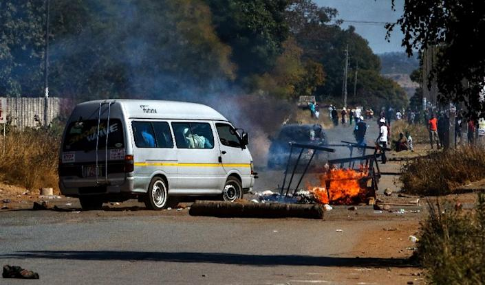 A public transport vehicle is blocked by burning tyres and barricades set up by protestors in Mufakose, Harare (AFP Photo/)