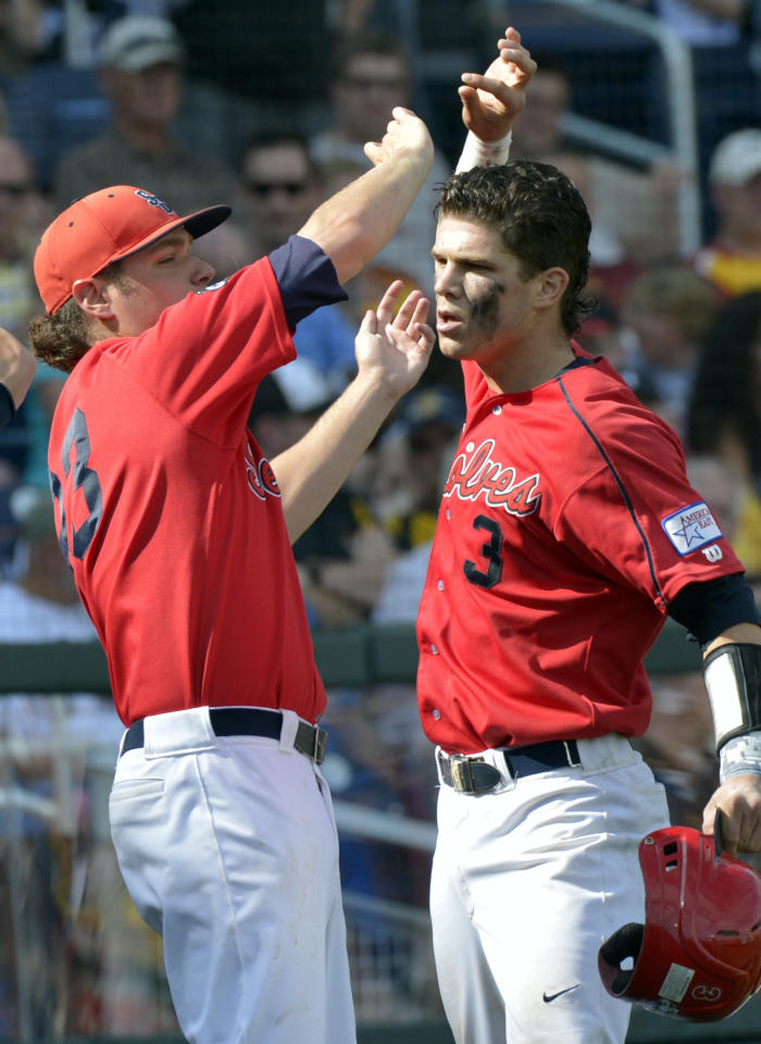 Stony Brook's Pat Cantwell, right, celebrates with teammates after hitting a solo home run against UCLA during the third inning of an NCAA College World Series baseball game in Omaha, Neb., Friday, June 15, 2012. (AP Photo/Ted Kirk)
