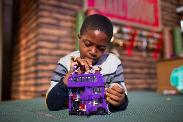 Peter Olunloyo, eight, plays with a Harry Potter Knight bus toy by Lego