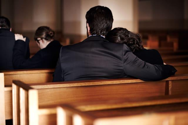 D2G2JW Rearview of a family of mourners sitting in pews at a church funeral service. Image shot 2012. brother; caucasian; ceremo