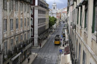 A tram drives through downtown Lisbon, Friday, June 18, 2021. Travel in and out of the Lisbon metropolitan area is to be banned over coming weekends as Portuguese authorities respond to a spike in new COVID-19 cases in the region around the capital. (AP Photo/Armando Franca)
