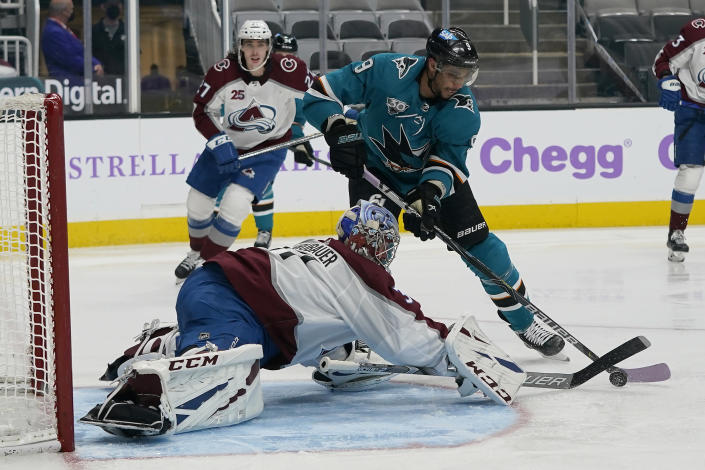 Colorado Avalanche goaltender Philipp Grubauer, bottom, defends a shot by San Jose Sharks left wing Evander Kane (9) during the third period of an NHL hockey game in San Jose, Calif., Monday, May 3, 2021. (AP Photo/Jeff Chiu)