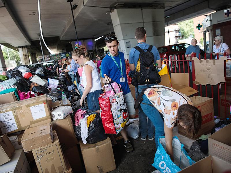 Volunteers sort through donations for victims near to the site of the Grenfell Tower fire: Getty