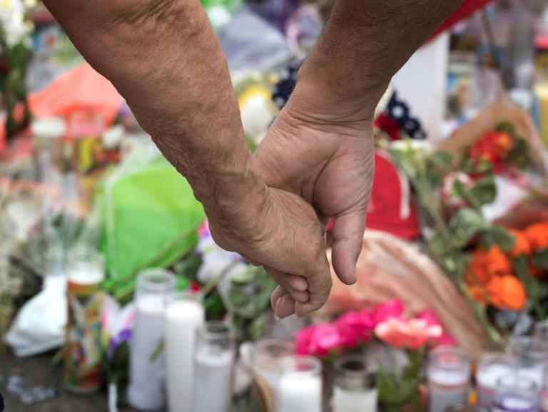 An elderly couple hold hands at a makeshift memorial for victims of a mass shooting in El Paso, Texas the first of back-to-back massacres that have galvanized supporters of tougher gun laws (AFP Photo/Mark RALSTON)