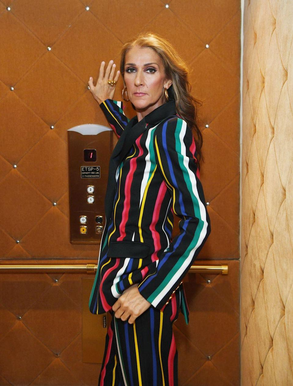 <p>A power suit lends itself to a power pose. Dion celebrated being named L'Oreal's global spokeswoman with this multicolored suit, the perfect balance of whimsy and business. </p>