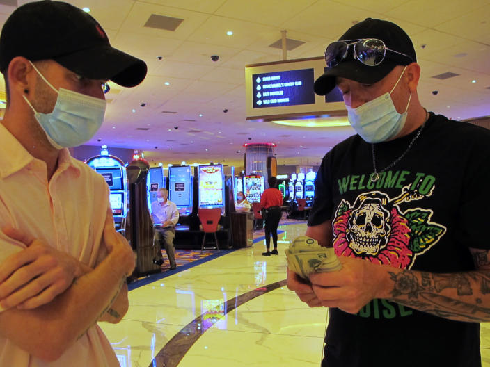 Gamblers count their money before starting to make bets at the Hard Rock casino in Atlantic City, N.J., on July 2, 2020, the day it reopened after being closed for just over three months due to the coronavirus outbreak. New Jersey's casinos and horse tracks won $2.88 billion in 2020, a decrease of nearly 17% from 2019, according to figures released Wednesday, Jan. 13, 2021, by the New Jersey Division of Gaming Enforcement. (AP Photo/Wayne Parry)