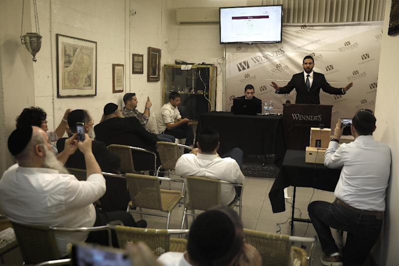 Auctioneer Gal Wiener of the Winner's auction house in Jerusalem gestures during an auction on October 24, 2017 that saw a note written by Albert Einstein in 1922 fetch $1.56 million (AFP Photo/MENAHEM KAHANA)