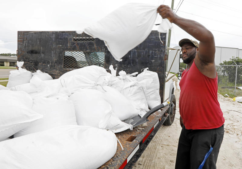 Travis Lee loads filled sand bags onto a truck bed as he and a co-worker prepare to protect the storage company they work at, Saturday, May 26, 2018 in Gulfport, Miss. They and many other Gulf Coast residents are preparing for Subtropical Storm Alberto to make its way through the Gulf of Mexico to land. The slow moving storm is threatening to bring heavy rainfall, storm surges, high wind and flash flooding this holiday weekend. (AP Photo/Rogelio V. Solis)