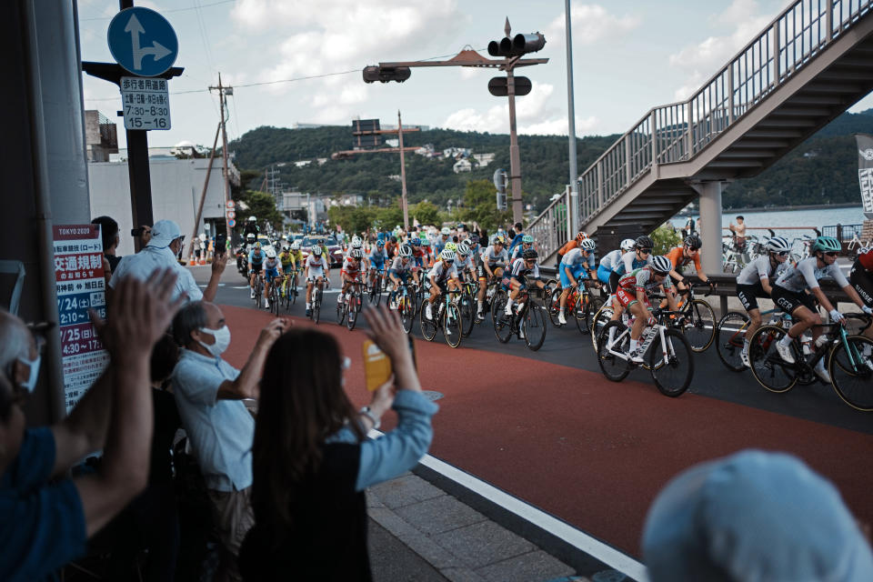 Fans watch as athletes compete during the women's cycling road race at the 2020 Summer Olympics, Sunday, July 25, 2021, in Oyama, Japan. (AP Photo/Thibault Camus)