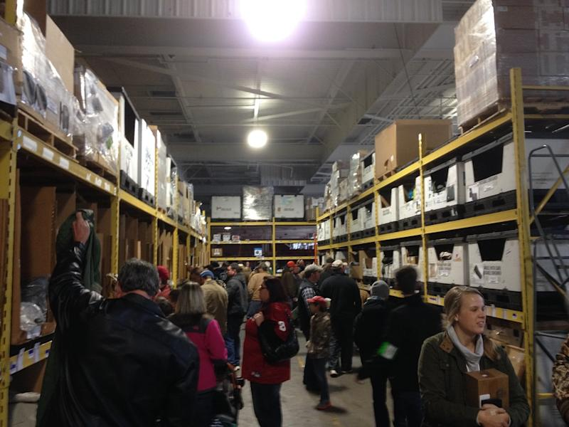 Shoppers in an aisle in a warehouse with shelves to the ceiling with products.