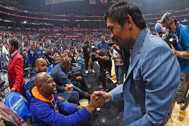Floyd Mayweather and Manny Pacquiao greet each other during the game between the Charlotte Hornets and Los Angeles Clippers on Jan. 8, 2019 at Staples Center in Los Angeles. (Andrew D. Bernstein/NBAE via Getty Images)