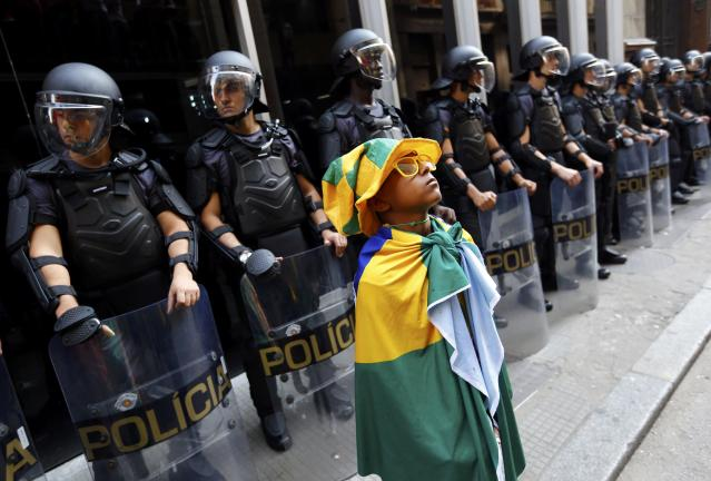 A young soccer fan stands in front of a police line during the fifth day of metro worker's protest in Sao Paulo June 9, 2014. Brazilian police used tear gas on Monday to disperse metro workers on strike in Sao Paulo in defiance of a court order to return to work, causing major traffic congestion just three days before the city hosts the opening match of the World Cup soccer tournament. REUTERS/Kai Pfaffenbach (BRAZIL - Tags: BUSINESS EMPLOYMENT SOCCER SPORT TRANSPORT CIVIL UNREST WORLD CUP)