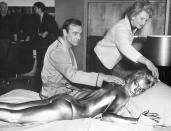 "FILE - In this file photo dated April 20, 1964, James Bond, alias, Sean Connery, finds himself in a sticky situation with actress Shirley Eaton at Pinewood Studios, near London. Miss Eaton was given a liberal coating of gold paint for a scene in the latest Bond thriller ""Goldfinger,"" with unidentified woman at top. Scottish actor Sean Connery, considered by many to have been the best James Bond, has died aged 90, according to an announcement from his family. (AP Photo/Victor Boynton)"