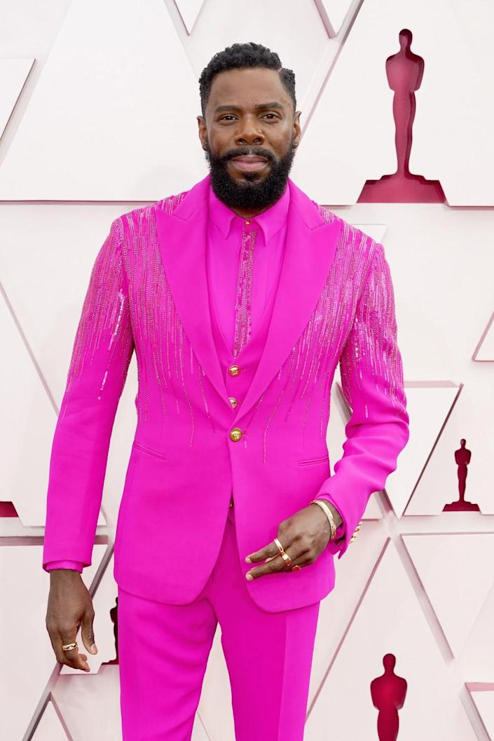 Colman Domingo arrives at the Oscars in a bright dark pink suit and shirt.