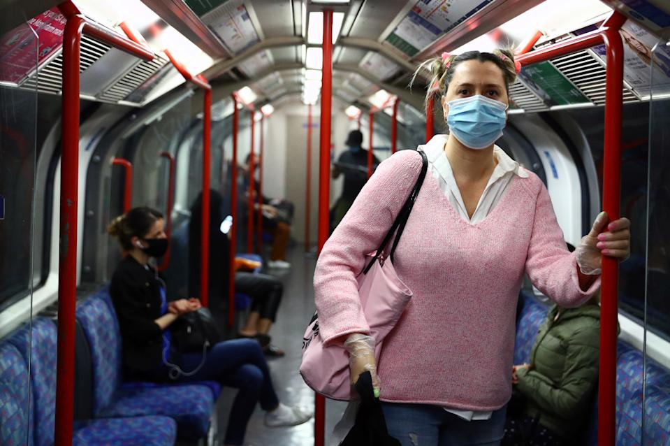 A passenger wearing a face mask travels on the Central line tube, in London. Photo: Hannah McKay/Reuters