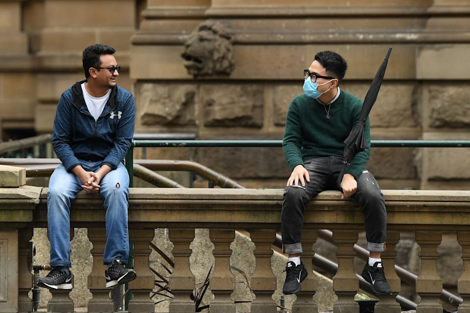 Two men sit on a wall in Sydney, one wearing a face mask. Source: AAP