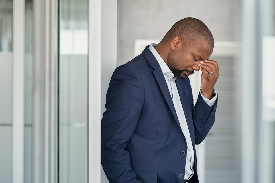 Stressed mature business man rubbing eyes standing in office. African american businessman in formal clothing feeling tired rubbing nose and eyes, for fatigue and headache. Depressed and anxious man in office feeling frustrated after layoff.