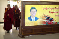 Monks walk past a mural with a portrait of Chinese President Xi Jinping and the Tiananmen Gate at the Tibetan Buddhist College near Lhasa in western China's Tibet Autonomous Region, Monday, May 31, 2021, as seen during a government organized visit for foreign journalists. High-pressure tactics employed by China's ruling Communist Party appear to be finding success in separating Tibetans from their traditional Buddhist culture and the influence of the Dalai Lama. (AP Photo/Mark Schiefelbein)