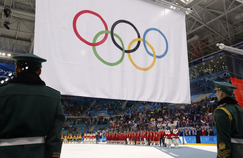 Olympic Athletes from Russia wear their gold medals under the Olympic flag during the victory ceremony.