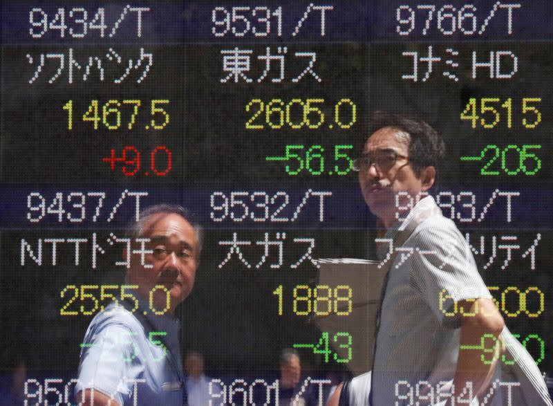 FILE PHOTO: Passersby are reflected on a stock quotation board outside a brokerage in Tokyo