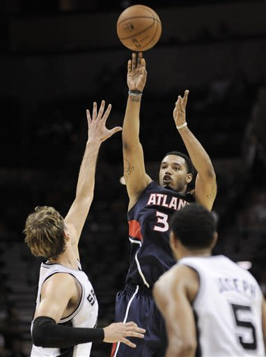 Atlanta Hawks' Mike Scott, center, shoots over San Antonio Spurs' Tiago Splitter, left, of Brazil, and Cory Joseph, to tie the game with seconds left in the second half of an NBA preseason basketball game, Wednesday, Oct. 10, 2012, in San Antonio. San Antonio won 101-99. (AP Photo/Darren Abate)