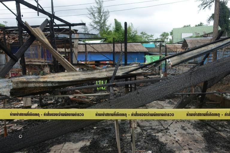 Police tape cordons off burned buildings at the site of a small bomb blast and arson attack on a market in Takua Pa, Phang Nga province, on August 12, 2016