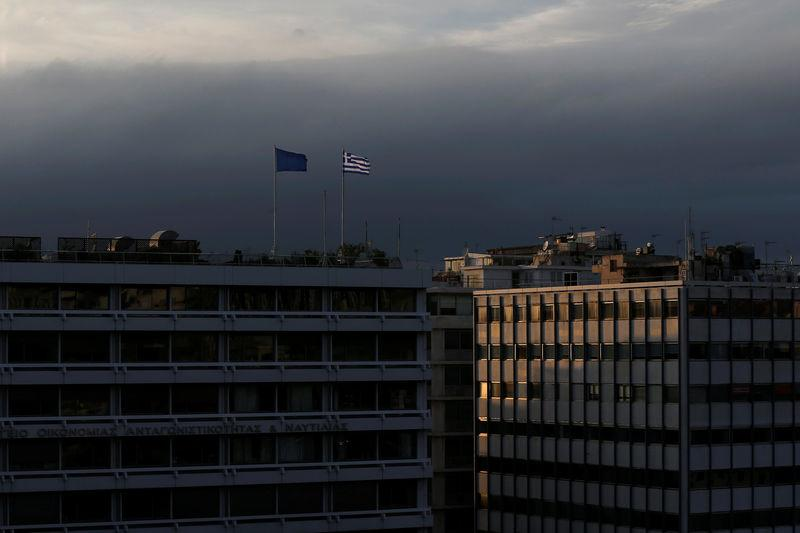 FILE PHOTO: A Greek national flag and a European Union flag flutter atop the Finance Ministry building during sunset in Athens