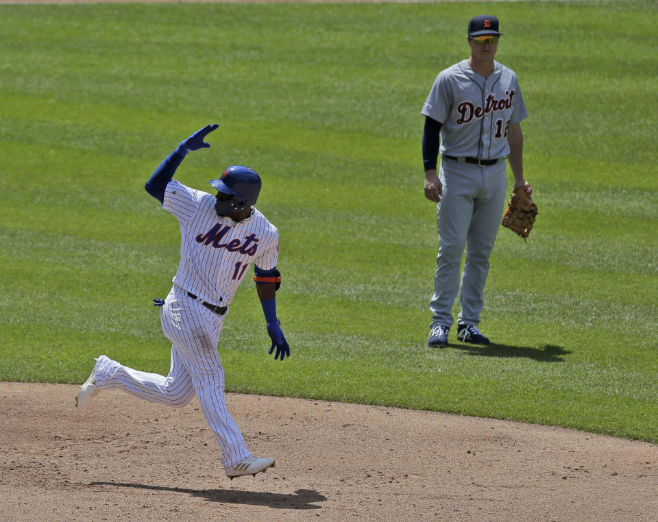 As Detroit Tigers first baseman Brandon Dixon, right, looks on, New York Mets' Adeiny Hechavarria reacts after hitting a three-run home run during the fourth inning of a baseball game at Citi Field, Sunday, May 26, 2019, in New York. (AP Photo/Seth Wenig)