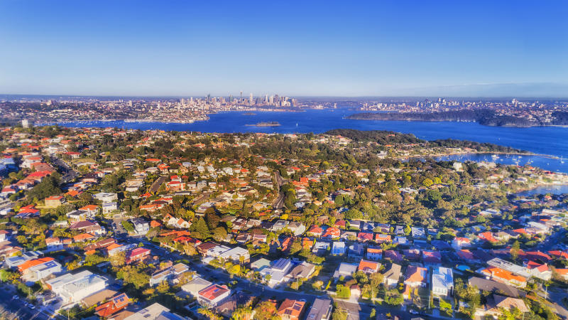 Eastern suburbs of Sydney in aerial view across Sydney harbour towards distant city CBD high-rise towers and waterfront under soft morning light on a bright clear day.