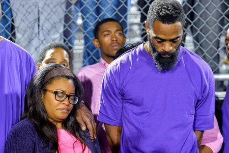 Shoshana Boyd (L) and Olympic sprinter Tyson Gay stand surrounded by those gathered during a candlelight vigil at Lafayette High School for their daughter Trinity Gay, who died in an exchange of gunfire early Sunday morning, in Lexington, Kentucky, October 17, 2016. REUTERS/Bryan Woolston