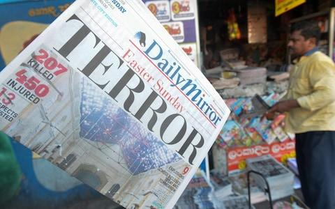 he front page of a Sri Lankan newspaper, showing coverage of the Easter Sunday blasts, hangs at a newsstand in Colombo  - Credit: AFP