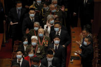 Delegates wearing face masks to help curb the spread of the coronavirus applaud as masked veteran soldiers arrive to attend the commemorating conference on the 70th anniversary of China's entry into the 1950-53 Korean War, at the Great Hall fo the People in Beijing, Friday, Oct. 23, 2020. (AP Photo/Andy Wong)